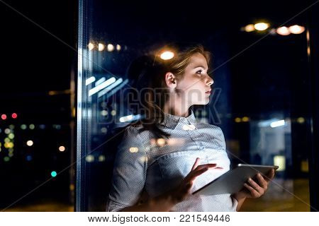 Beautiful young businesswoman with tablet in the office working late at night. Shot through glass.