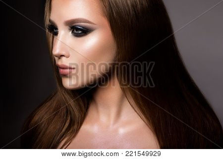 Glamour portrait of beautiful girl model with makeup and romantic hairstyle. Fashion shiny highlighter on skin, sexy gloss lips make-up and dark eyebrows. poster