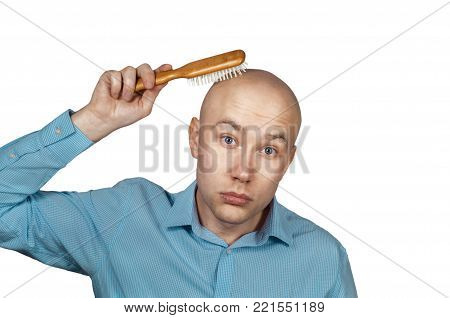 White balding man combing his bald head comb