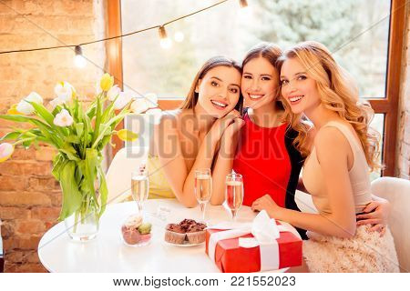 Three Pretty, Nice, Confident, Successful Girls Sitting In Restaurant, Embracing, Having Glasses Wit