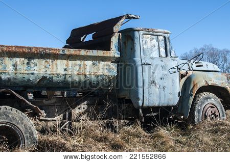 Old abandoned dirty broken vintage truck in the middle of paintball field playground