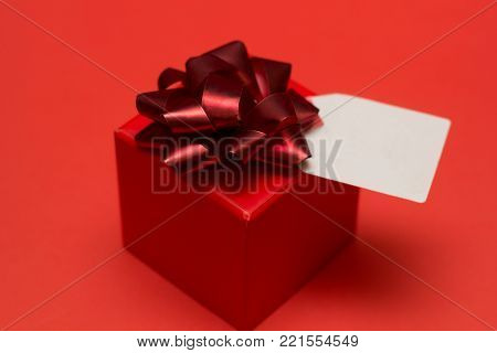 gift box with bow  and white lable on a red background