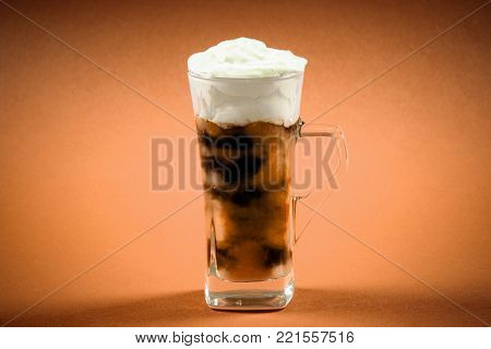 The ice coffee drink with whipped cream is on beige background.