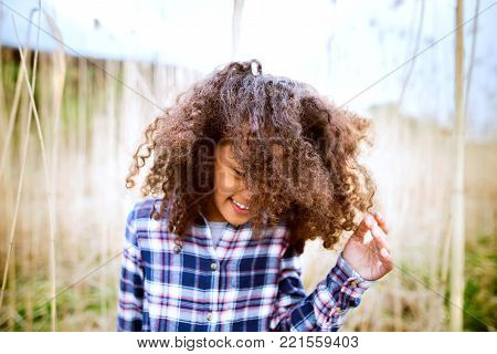 Beautiful african american girl with curly hair in checked shirt outdoors in field.