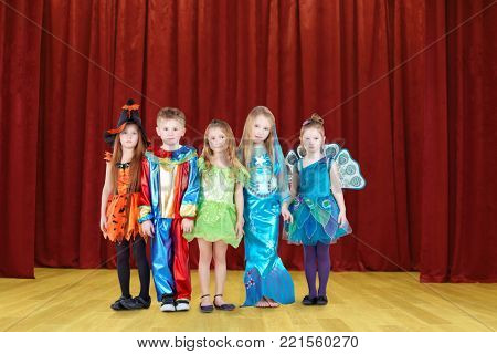 Five happy funny children in costumes on red stage, collage