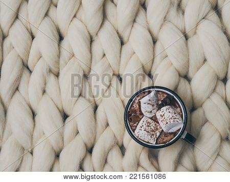 Cozy composition, hot chocolate with marshmallows, merino wool blanket, warm and comfortable atmosphere. Knit background. Flat lay. Top view. Copy space. Autumn concept.