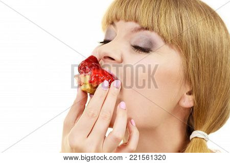 Woman holds cake cupcake in hand taking a huge bite out of dessert, eating unhealthy junk food. Sweetness indulging and fattening concept