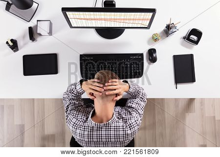 Elevated View Of A Frustrated Business Man In Front Of Computer At Office