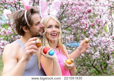 girl or pretty woman and handsome man or macho with bunny ears holding colorful eggs on floral environment. Happy girlfriend and boyfriend in blossoming garden. Couple in love. Spring. Easter