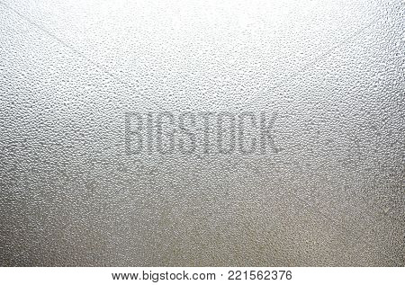 A photo of the glass surface of the window, covered with a multitude of droplets of various sizes. Background texture of a dense layer of condensate on glass