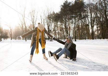 Beautiful senior couple in sunny winter nature ice skating, woman helping man to stand up.