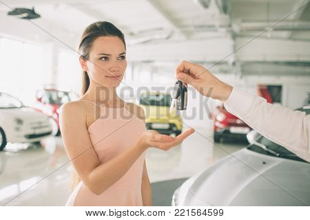 Beautiful young woman is holding a key in car dealership. Auto business, car sale, - happy female model in auto show or salon.