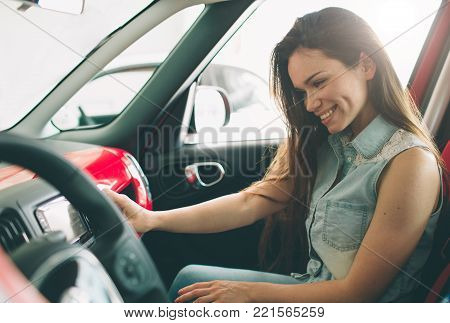 beautiful young woman buying a car at dealership. Female model sitting inside vehicle in showroom.