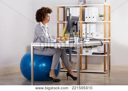 Young Businesswoman Using Computer While Sitting On Fitness Ball In Office