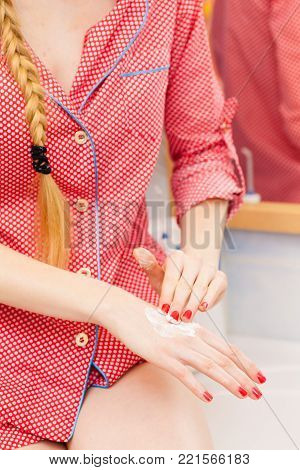 Body care concept. Woman applying moisturizing hand cream on hands and nails.
