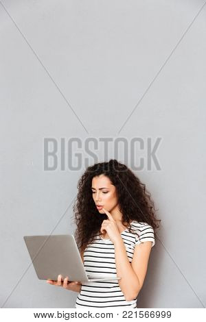 Concentrated female student with curly hair standing with notebook in hands studying hard, or reading interesting ebook over grey background