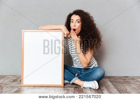 Funny portrait of adult girl in jeans sitting in lotus pose on the floor expressing embarrassment and surprise, while holding picture in frame copy space