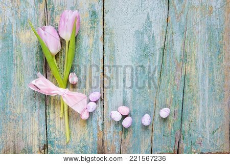 Easter composition with two pink tulip flowers tied with pink silk ribbon, end painted Easter eggs on the old blue wooden background, with copy-space, top view