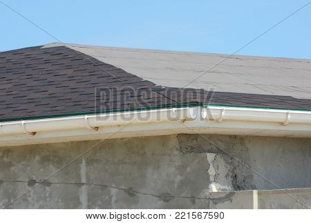 Installing asphalt shingles. Roof repair with unfinished rain gutter. Roofing construction with roof tiles, asphalt shingles.