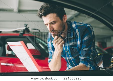 Perfect lines. The young dark-haired bearded man examining car at the dealership and making his choice. Horizontal portrait of a young guy at the car. He is thinking if he should buy it