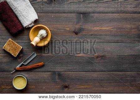 Men's shaving. Razor and brush on dark wooden background top view.