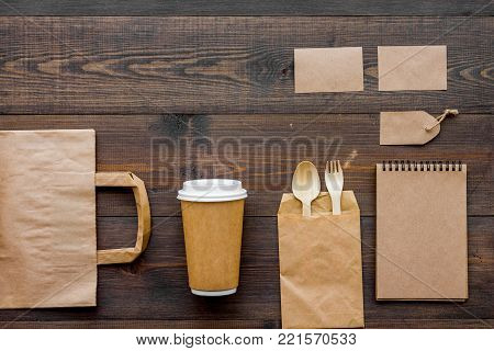 Craft paper color set. Paper bag, disposable tableware, notebook on wooden background top view.