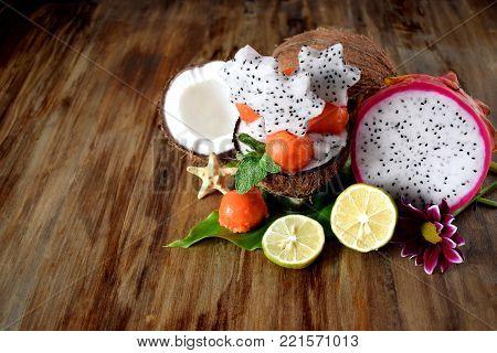 Tropical fruits. Papaya balls, coconuts, limes and pitahaya carved stars on a wooden table