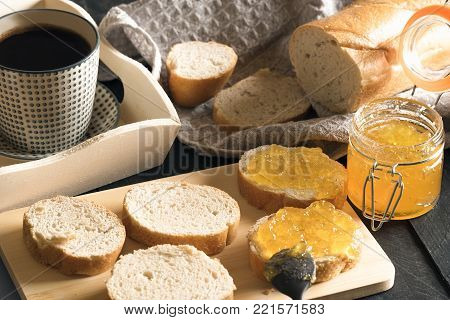 Sliced french bread with peach jam and coffee - Breakfast with french bread, sliced on a wooden cutting board, and smeared with homemade peach jam and a cup of hot coffee on a white wooden tray.