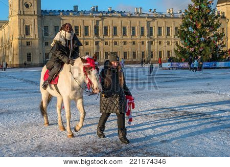 Gatchina, Russia - January 7, 2018: Gatchina Palace, New Year's Fair on the main stage. A festive attraction is riding a horse around a Christmas tree.