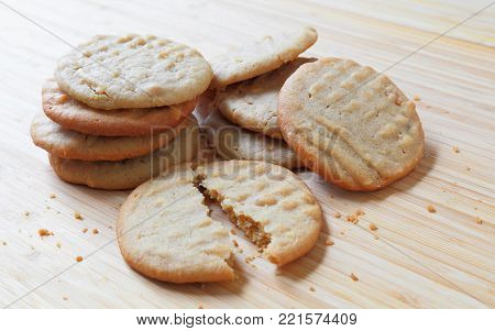 A batch of homemade peanut butter cookies on a wooden table.