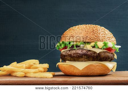 Fast food. Cheeseburger and french fries on a wooden board, on dark background. Still life. Copy space. Burger, hamburger