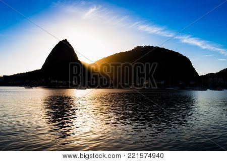 Silhouette of the Sugarloaf Mountain with Sun Rising Behind It, Rays of Light Visible