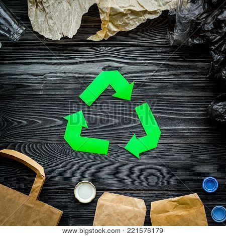 Green paper recycling sign among waste materials paper, plastic, polyethylene on grey wooden background top view.