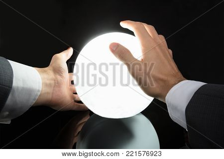 Close-up Of A Businessman's Hand Predicting Future With Glowing Crystal Ball