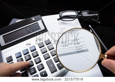 Close-up Of A Businessperson's Hand Analyzing Bill With Magnifying Glass