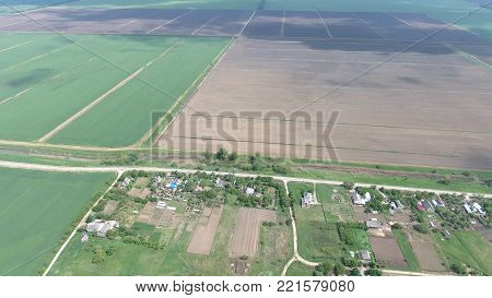 Top view of the village. One can see the roofs of the houses and gardens. Road the village. Village bird's-eye view.