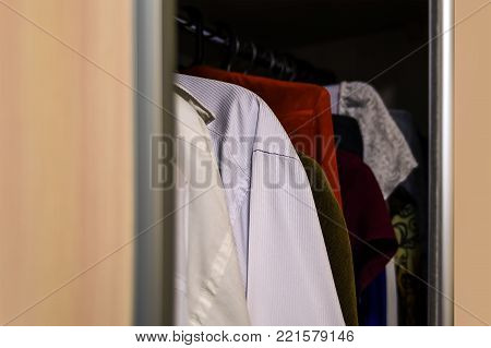 Wardrobe with clothes hanging on the rail.