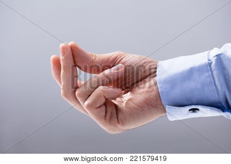 Close-up Of Man's Hand Snapping His Finger Against White Background