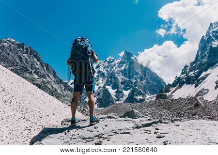 A mountaineer with a backpack stands on a rock and looks at a snowy peak, a back view, preparing for an ascent.