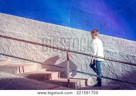 Young caucasian boy walking up stairs outdoors