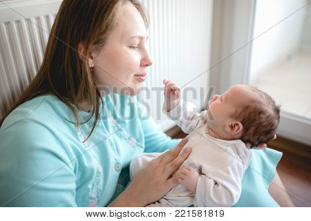 Happy Mother Holding Her Newborn Baby At Home