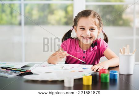 Happy smiling Little Girl Is Painting Picture