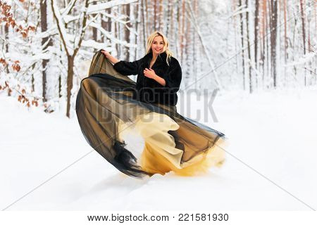 Young beautiful blond woman in a long black and yellow and golden dress in the snowy winter forest or wood outdoors