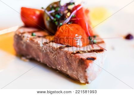 Macro view of the piece of grilled tuna fish with tomato slices and seasonings