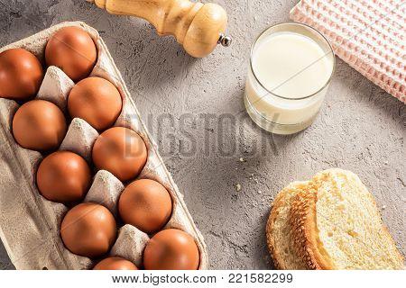 Farm raw fresh egg in pack bread milk on gray table ingredient for breakfast preparation scrambled eggs omelet fried egg