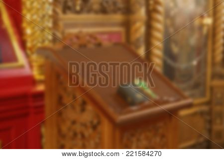 Analoy with the holy crucifix lying on it and the Gospel for the confession. Specially defocused image with blurred image.