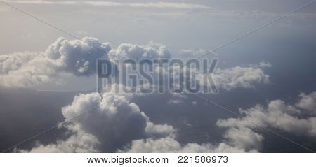 Clouds white and grey on dark blue sky background. Aerial photo from plane's window