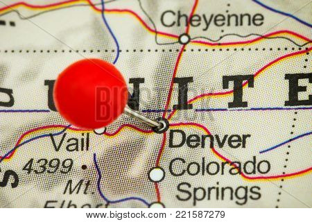 Close-up of a red pushpin on a map of Denver, USA.