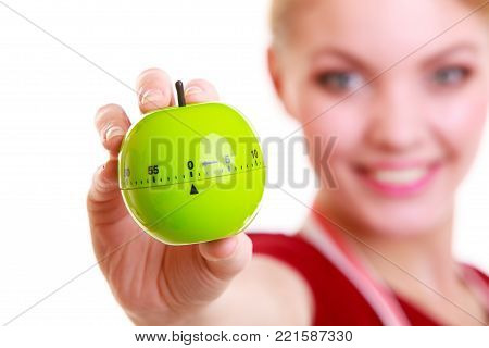 Happy housewife or chef in colorful kitchen showing apple timer eggtimer isolated studio shot