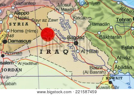 Close-up of a red pushpin on a map of Iraq.